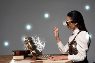 steampunk woman in goggles waving hand during video chat with glowing digital illustration isolated on grey
