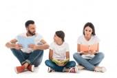 usmívající se rodina drží knihy, zatímco sedí izolované na bílém