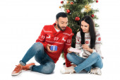 Fotografie happy man and woman holding gifts near christmas tree isolated on white