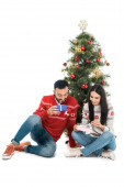 cheerful man and happy woman holding gifts near christmas tree isolated on white