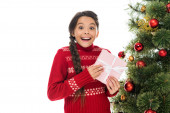 excited kid holding pink present near christmas tree isolated on white