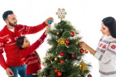 Fotografie happy daughter decorating christmas tree near parents isolated on white
