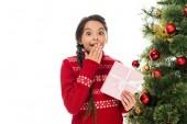 aufgeregtes Kind verdeckt Gesicht und hält rosafarbenes Geschenk in der Nähe des Weihnachtsbaums isoliert auf weiß