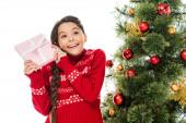 fröhliches Kind im Pullover hält Geschenk in der Nähe von Weihnachtsbaum isoliert auf weiß