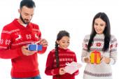 Fotografie glückliches Kind und Eltern betrachten Geschenke isoliert auf weiß
