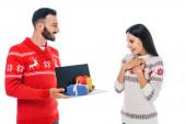 glücklicher Mann hält Laptop mit Geschenken nahe aufgeregter Frau isoliert auf weißem Grund