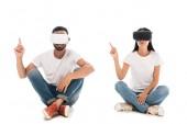 glücklicher Mann, der mit Frau sitzt, während er Virtual-Reality-Headsets benutzt und mit den Fingern auf weiß zeigt