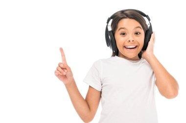 Happy kid listening music in headphones and pointing with finger isolated on white stock vector