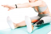 cropped view of disabled sportswoman stretching on fitness mat isolated on white