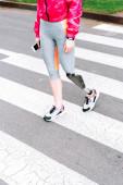 Fotografie částečný pohled postižené sportovkyně s protézou drží smartphone na ulici