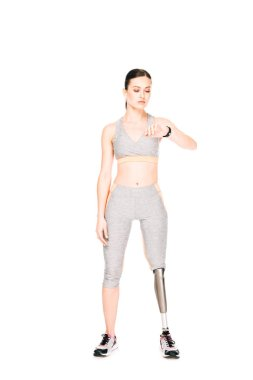 full length view of sportswoman with prosthetic leg looking at smartwatch isolated on white