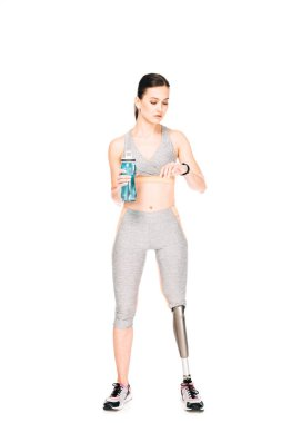 full length view of sportswoman with prosthetic leg holding sport bottle and looking at smartwatch isolated on white