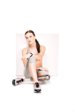 disabled sportswoman with prosthetic leg sitting on white