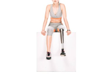 partial view of disabled sportswoman with prosthetic leg isolated on white