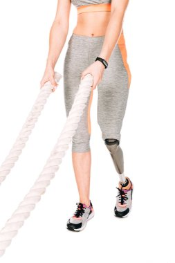 cropped view of disabled sportswoman with prosthetic leg training with ropes isolated on white