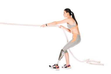 side view of disabled sportswoman training with rope isolated on white