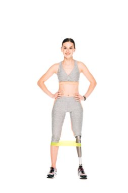 full length view of smiling disabled sportswoman with resistance band isolated on white