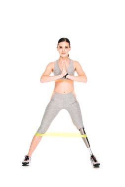 full length view of disabled sportswoman with resistance band isolated on white