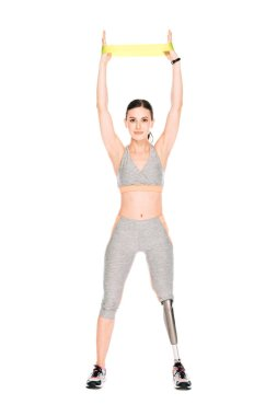 full length view of disabled sportswoman training with resistance band isolated on white