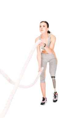 full length view of disabled sportswoman training with ropes isolated on white