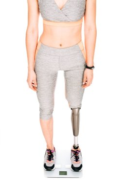 partial view of disabled sportswoman with prosthetic leg on weighing scale isolated on white