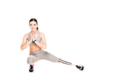 disabled sportswoman with prosthesis stretching isolated on white