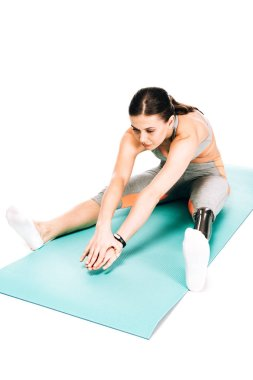 overhead view of disabled sportswoman stretching on fitness mat isolated on white
