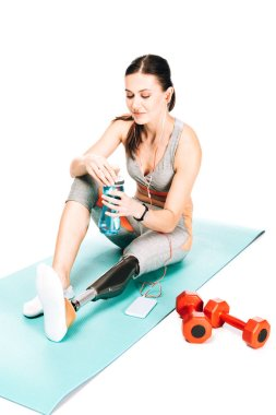 disabled sportswoman sitting on fitness mat and listening music in earphones isolated on white
