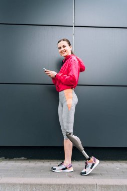 full length view of smiling disabled sportswoman with prosthesis using smartphone on street