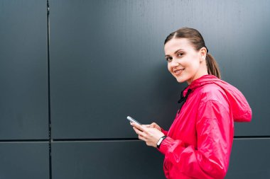 smiling attractive young woman holding smartphone on street