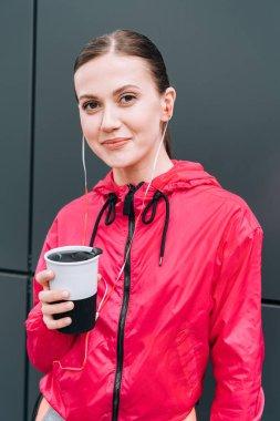 Gülümseyen sporcu kadın bardak tutuyor ve sokakta kulaklıkla müzik dinliyor.
