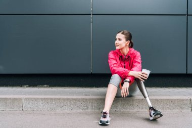 disabled sportswoman listening music in earphones and holding cup on street