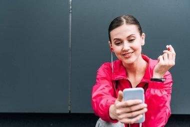smiling sportswoman in earphones using smartphone on street