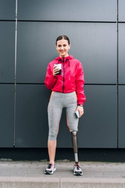 full length view of smiling disabled sportswoman holding smartphone and cup on street