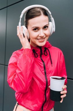 Smiling sportswoman holding cup and listening music in headphones on street stock vector