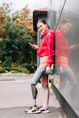 full length view of smiling disabled sportswoman with sport bottle and smartphone on street