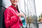 Teilbild einer lächelnden Sportlerin mit Sportflasche auf der Straße