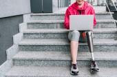 oříznutý pohled na usmívající se zdravotně postižené sportovkyně pomocí notebooku při sezení na schodech na ulici