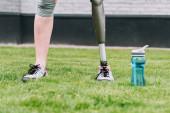 Teilbild einer behinderten Sportlerin, die neben Sportflasche auf Gras auf der Straße steht