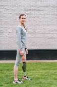 teljes hosszúságú kilátás mosolygós fogyatékkal élő sportoló álló fű