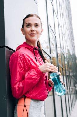 Smiling beautiful sportswoman holding sport bottle on street stock vector