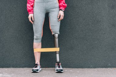partial view of disabled sportswoman with resistance band on street
