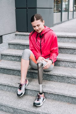 disabled sportswoman with prosthesis sitting on stairs on street