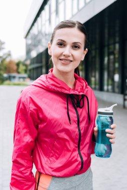 Attractive smiling sportswoman holding sport bottle on street stock vector