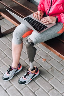 partial view of disabled sportswoman typing on laptop on street