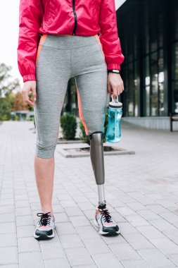 partial view of disabled sportswoman holding sport bottle on street