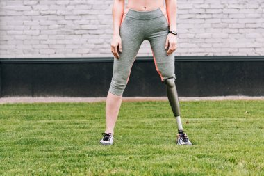partial view of disabled sportswoman with fitness tracker on grass