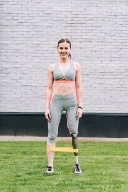 full length view of smiling disabled sportswoman training with resistance band on grass