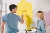 mladá žena drží váleček zásobník, zatímco přítel malování zeď ve žluté s nátěrem váleček