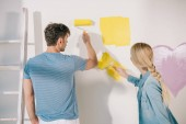 young couple painting white wall in yellow with paint rollers